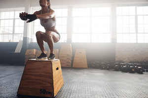 Fitness-woman-doing-box-jump-workout-at-crossfit-gym